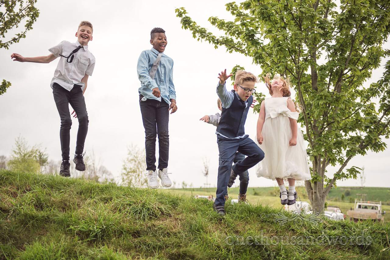 Young guests play in the gardens at Tithe Barn Symondsbury Wedding