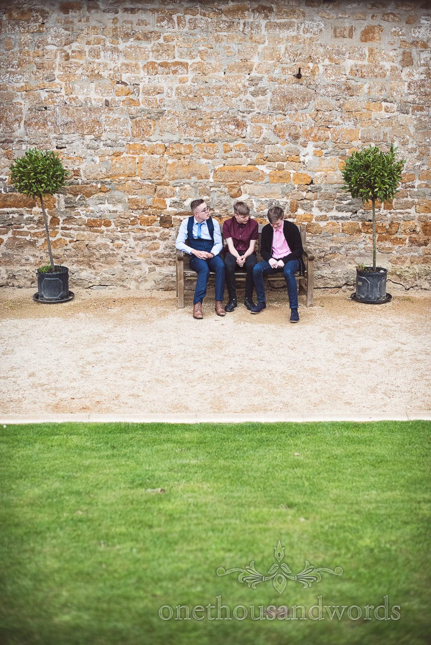 Young guests take a break on bench during Tithe Barn Symondsbury Wedding