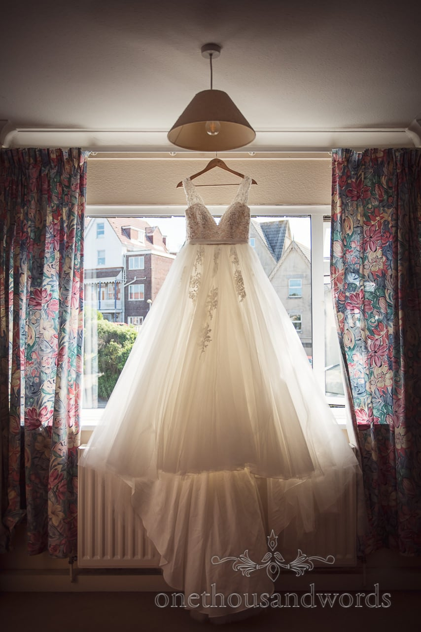 Ballgown style wedding dress hangs in window from Swanage wedding photos