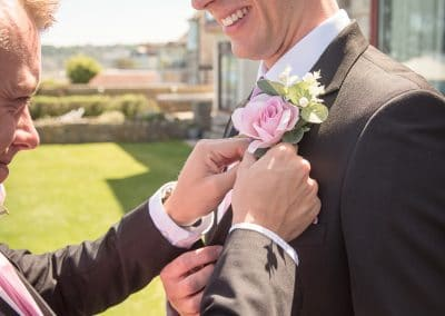 Best man helps groom with buttonhole from Swanage wedding photos