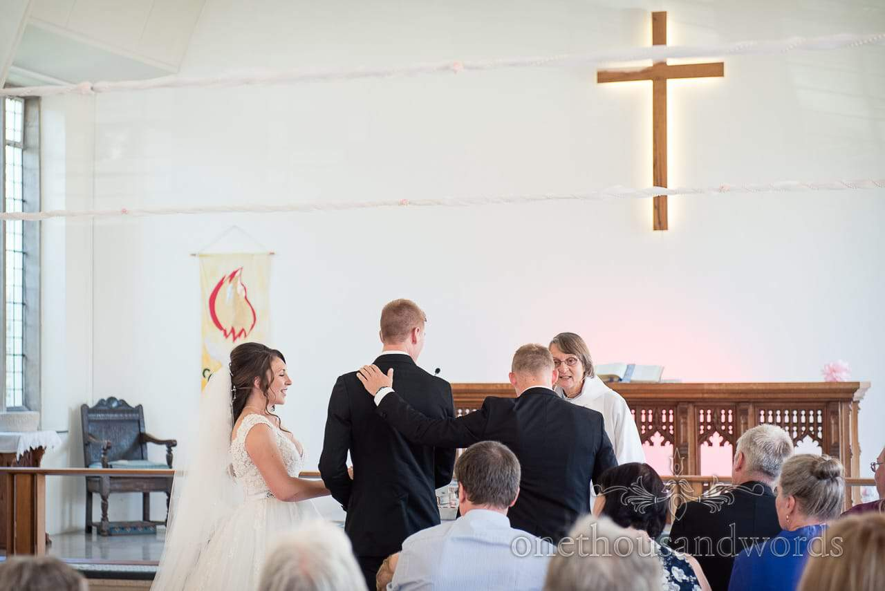 Best man puts hand on grooms shoulder during ceremony from Swanage wedding photos