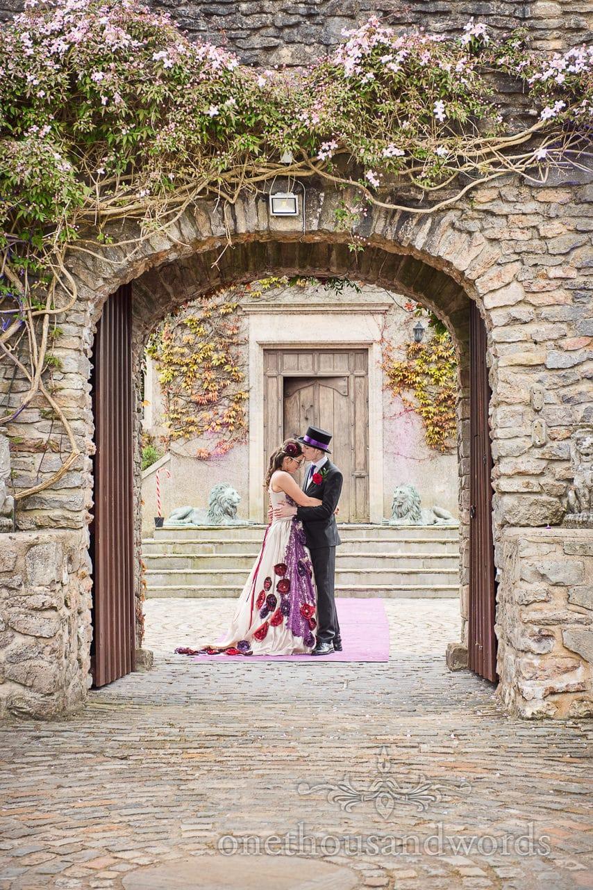 Bride adn groom kiss under entrance door way at Walton Castle wedding