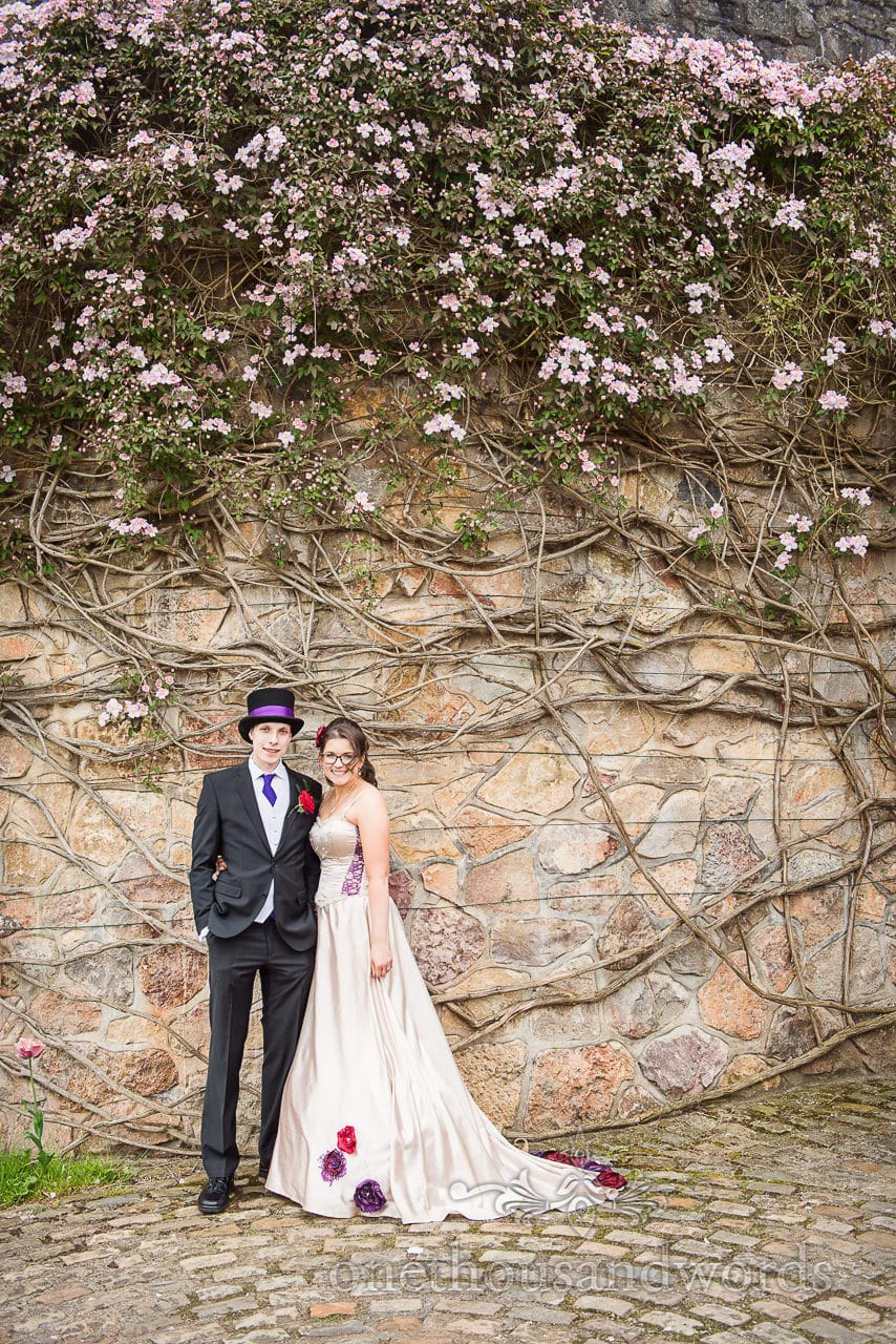 Bride and groom couple photographs under flowers at Walton Castle wedding