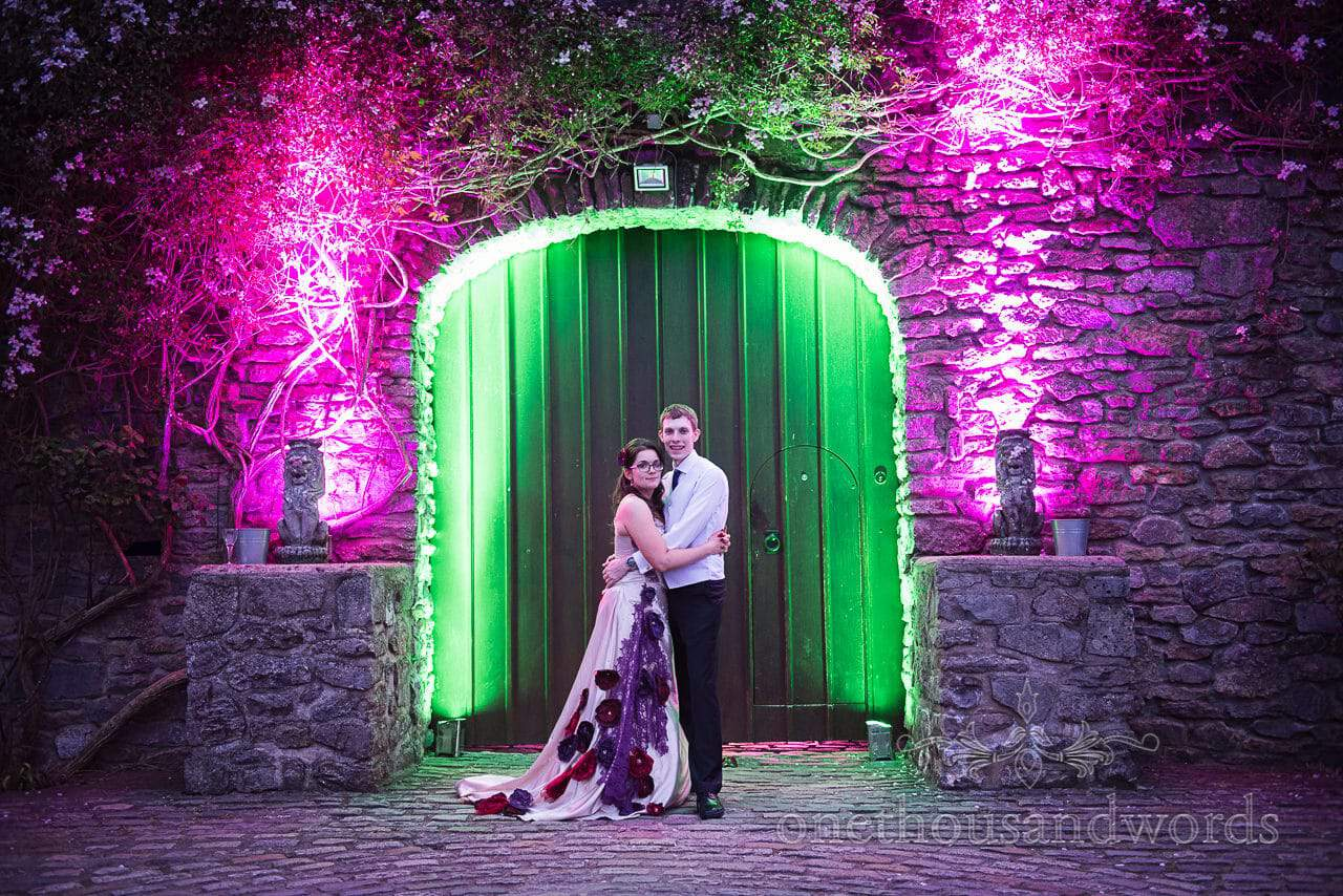 Bride and groom hug in front of castle door with pink and green lights