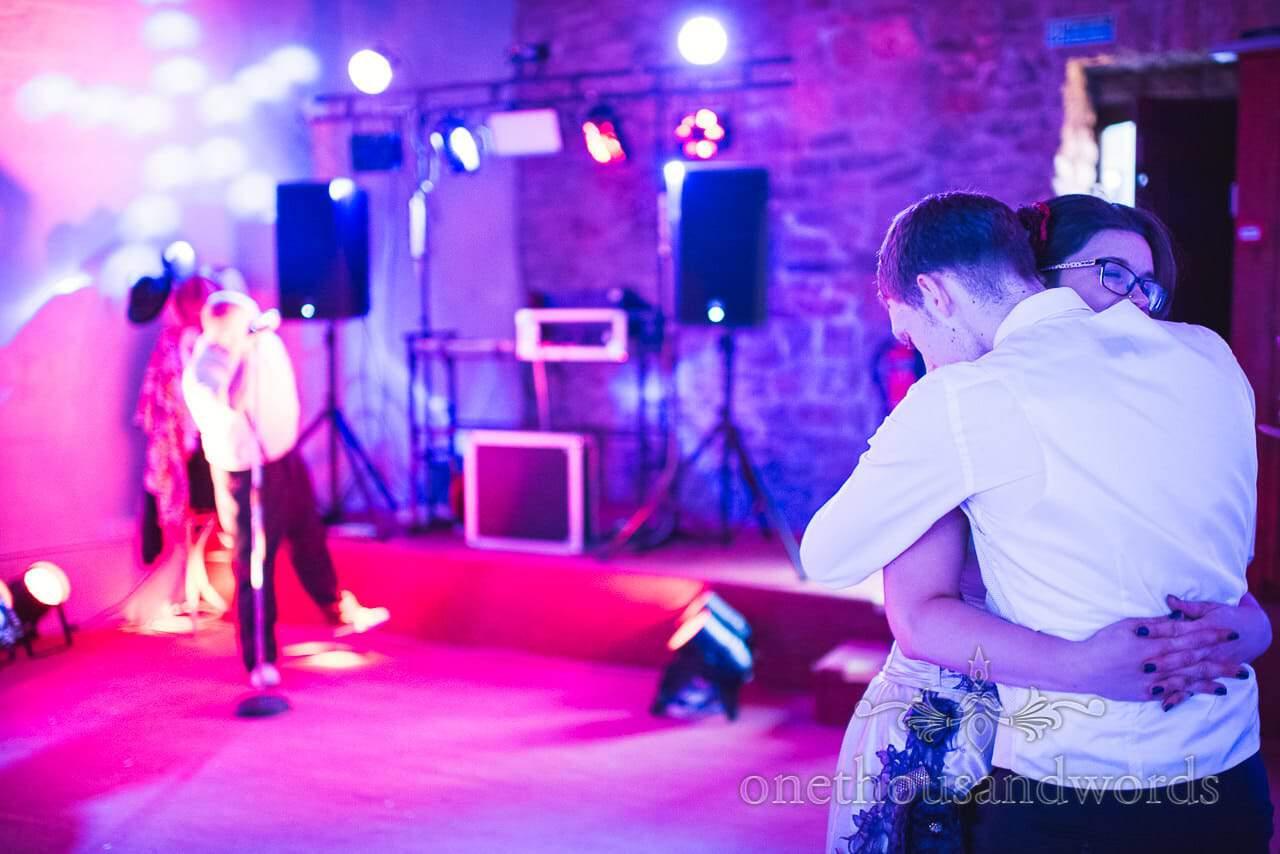 Bride and groom hug on wedding dance floor under disco lighting