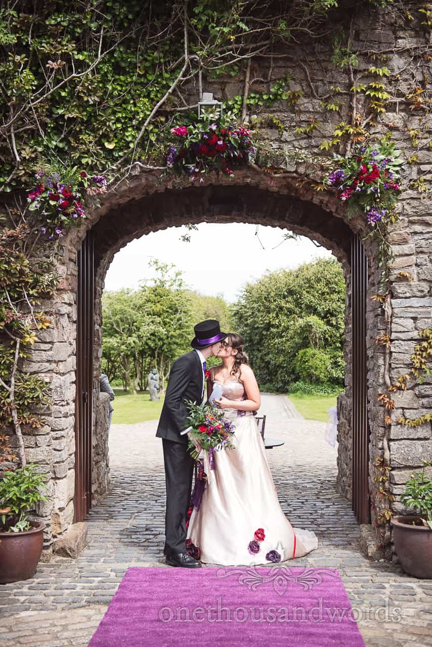Bride and groom kiss under archway at Chocolate Themed Wedding Photographs