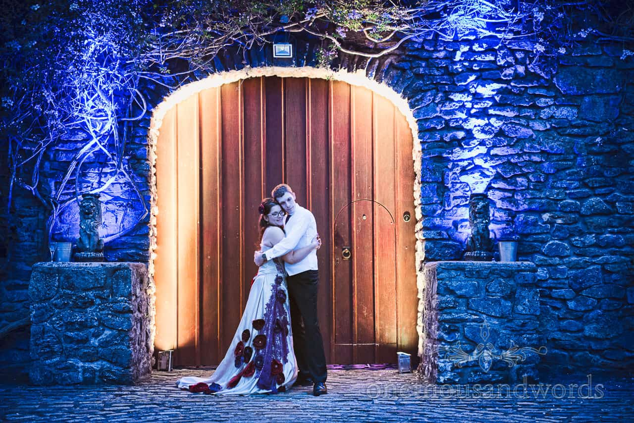 Bride and groom outside a castle door with white and blue lighting