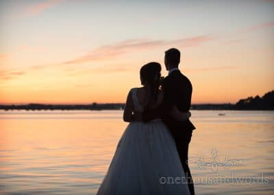 Bride and groom share embrace and the sunset from Swanage Wedding Photos