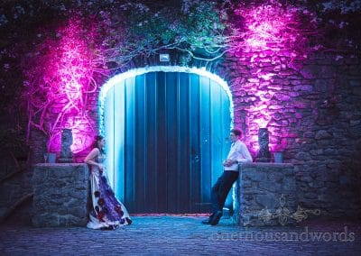 Bride and groom with purple and blue lighting outside Walton Castle door