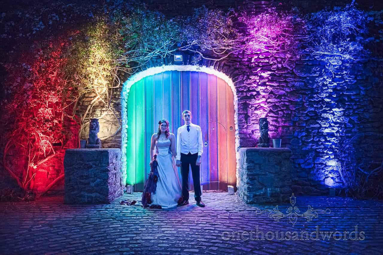 Bride and groom with rainbow lighting at Walton Castle wedding venue