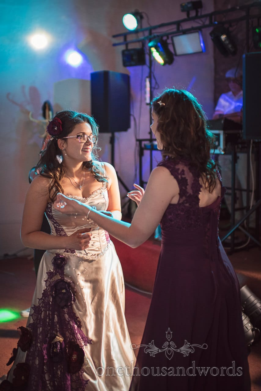 Bride and sister dance under disco lights to wedding DJ at Walton Castle