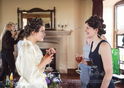 Bride and sister enjoy cocktails on wedding morning with curlers in hair