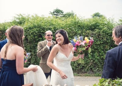 Bride, bridesmaid and father make there way to wedding car from Countryside Wedding Photos