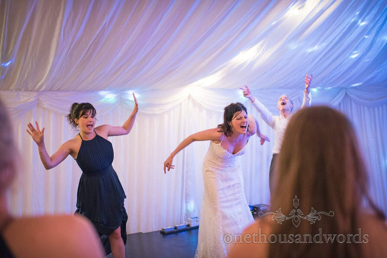 Bride, bridesmaid and friend perform dance routine on wedding marquee stage