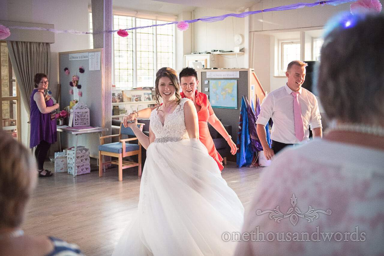 Bride dances with guest during evening reception from Swanage wedding photos