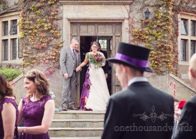 Bride exits castle door into wedding ceremony at Walton Castle