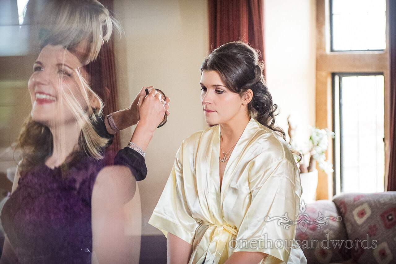 Bride has make up styled while maid of honour looks on from Chocolate Themed Wedding Photographs