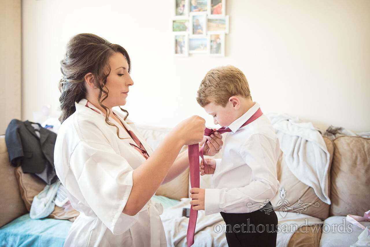 Bride helps son with pink tie on morning of Swanage Wedding Photos