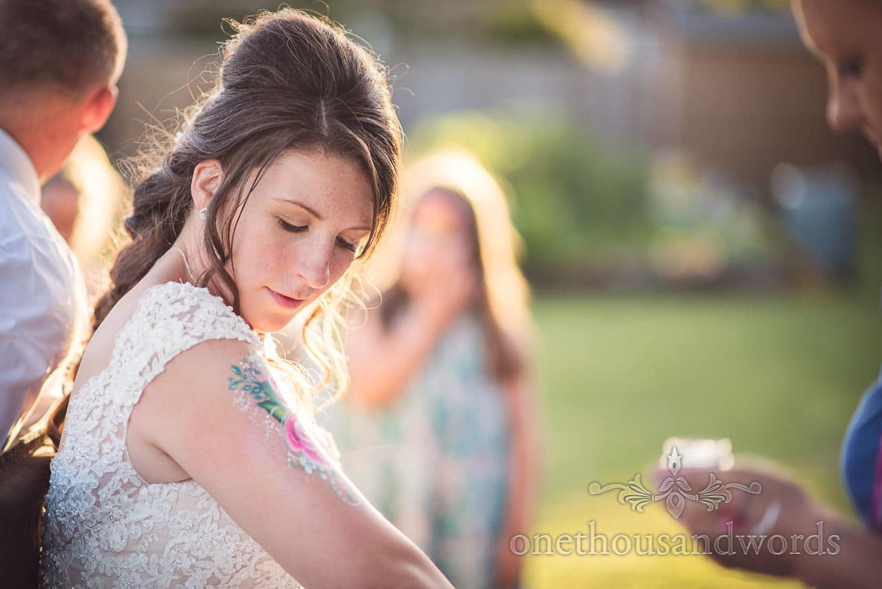 Bride looks at temporary tattoo from Swanage wedding photos