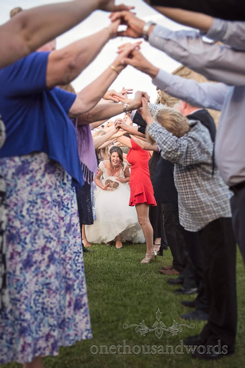 Bride makes here way down guest guard of honor from Swanage Wedding Photos