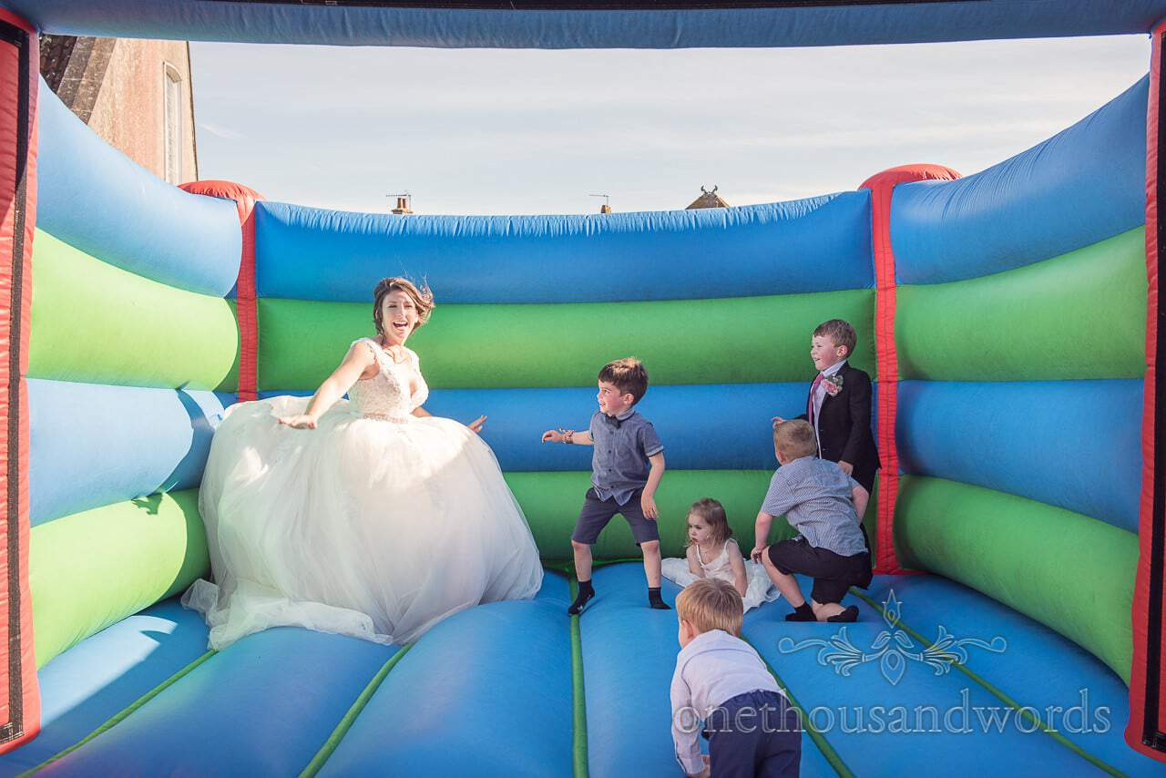 Bride on bouncy castle with children from Swanage wedding photos