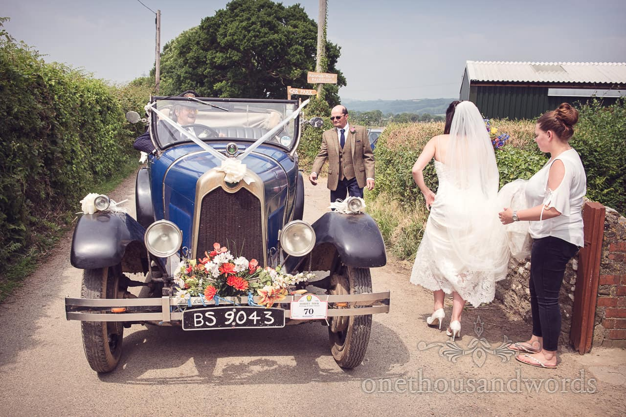 Bride readies herself to get into classic wedding car with father from Countryside Wedding Photos