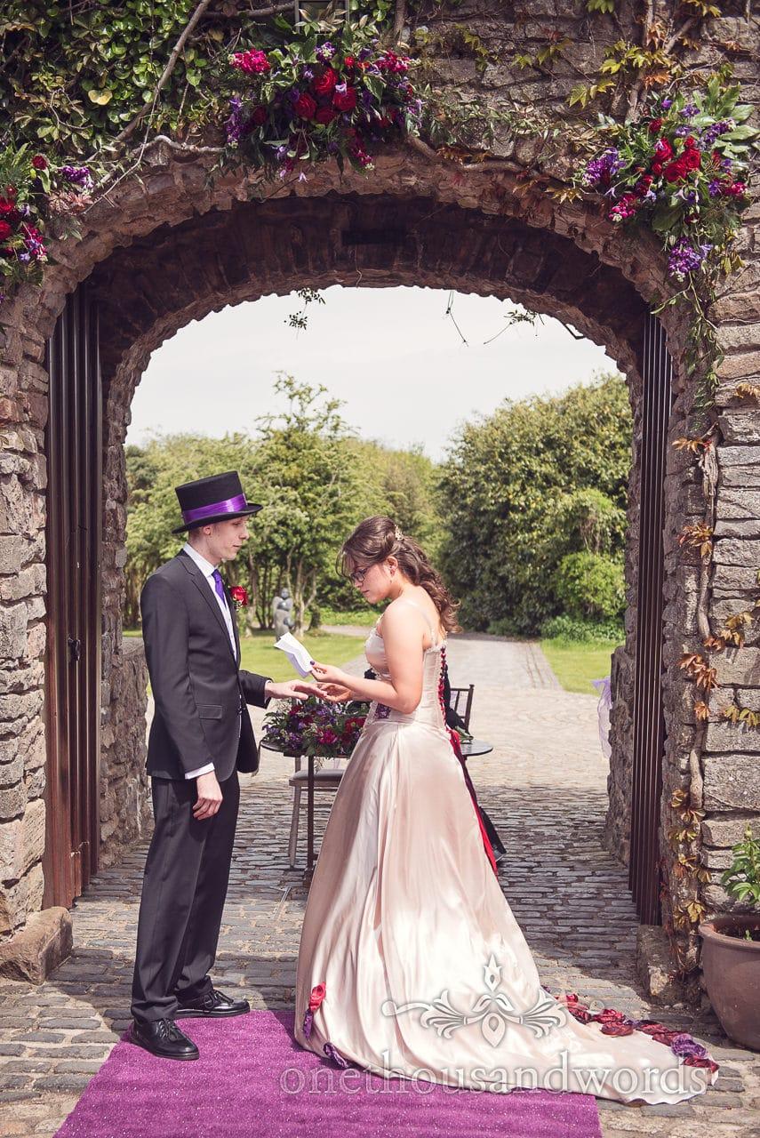 Bride reads vows to groom under castle archway at Walton Castle wedding venue