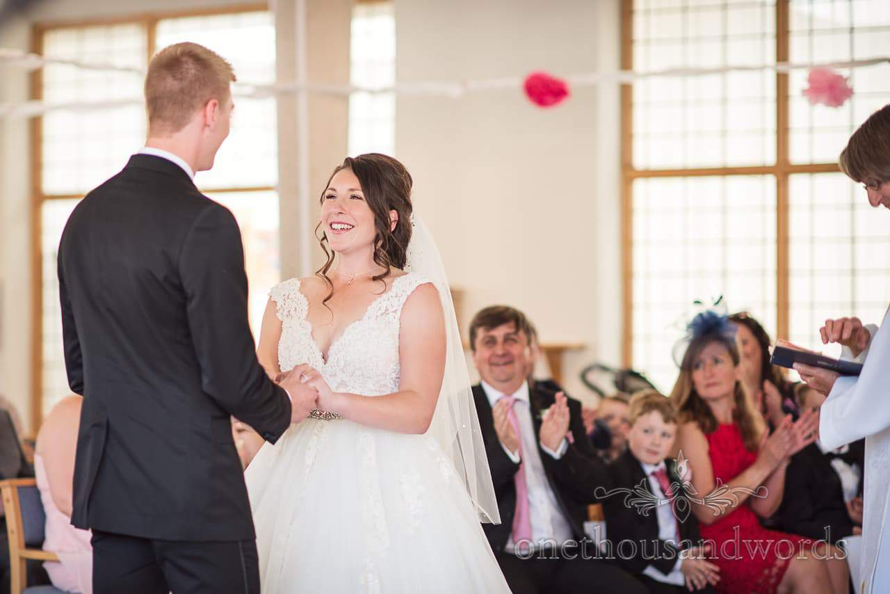Bride smiles during wedding ceremony at All Saints church in Swanage