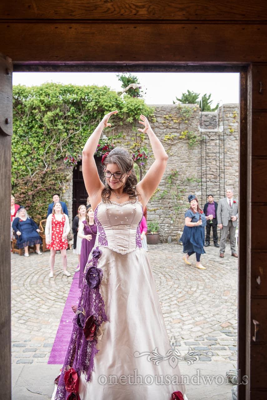 Bride throwing wedding bouquet in doorway at Walton Castle wedding