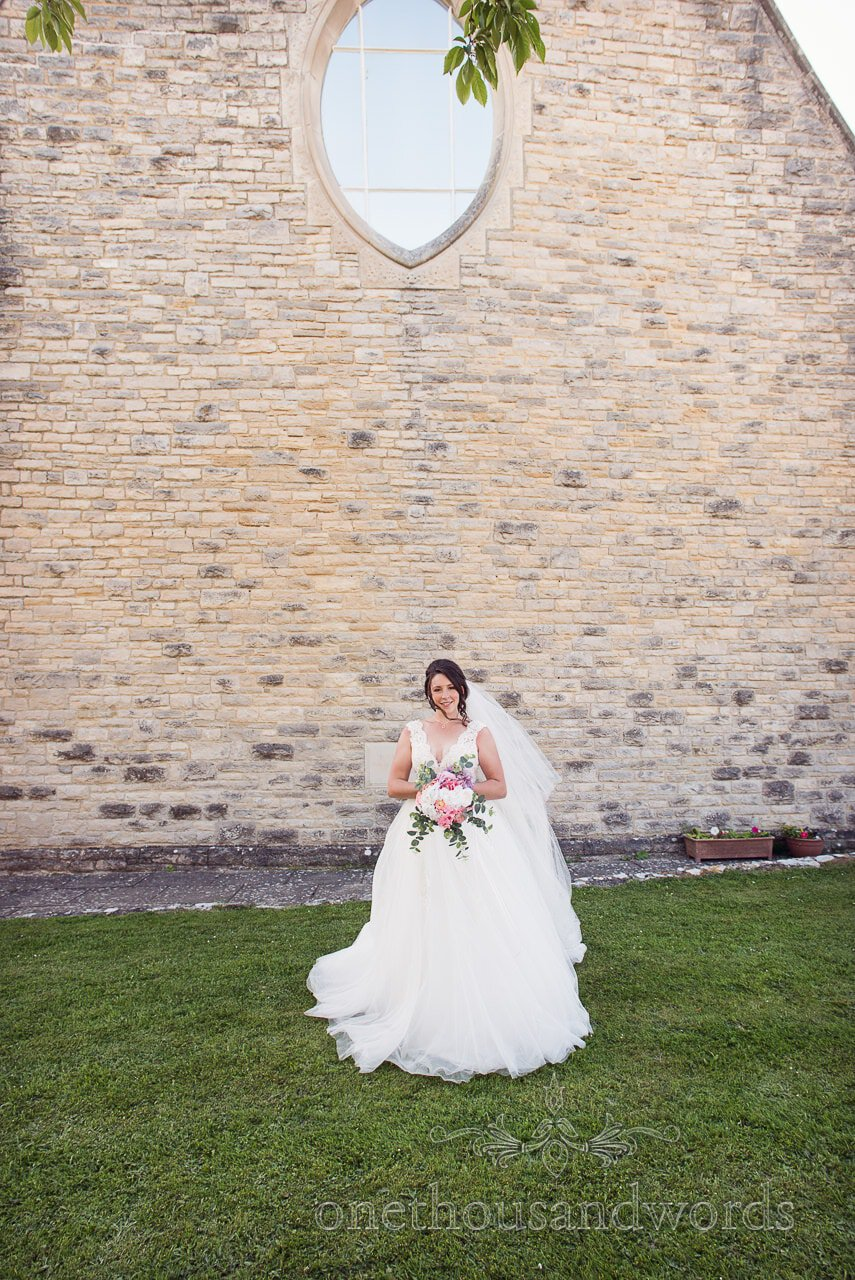 Bride will ball gown style wedding dress outside All Saints church in Swanage