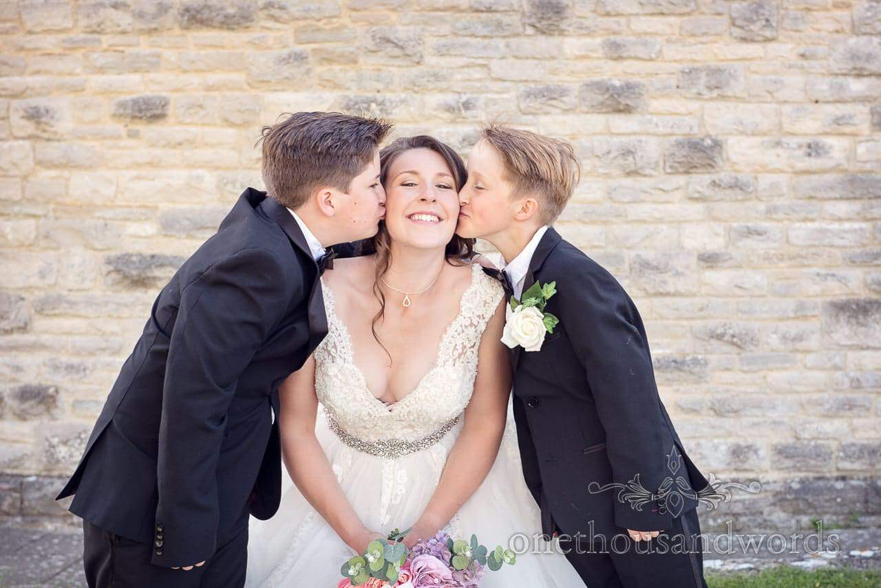 Bride with brothers outside church from Swanage wedding photos