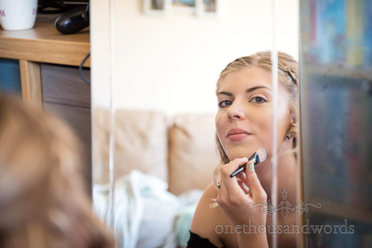 Bridesmaid armed with make up brush in mirror from Swanage Wedding Photos