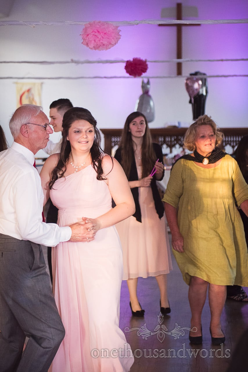 Bridesmaid dances with guest during evening entertainment from Swanage Wedding Photos