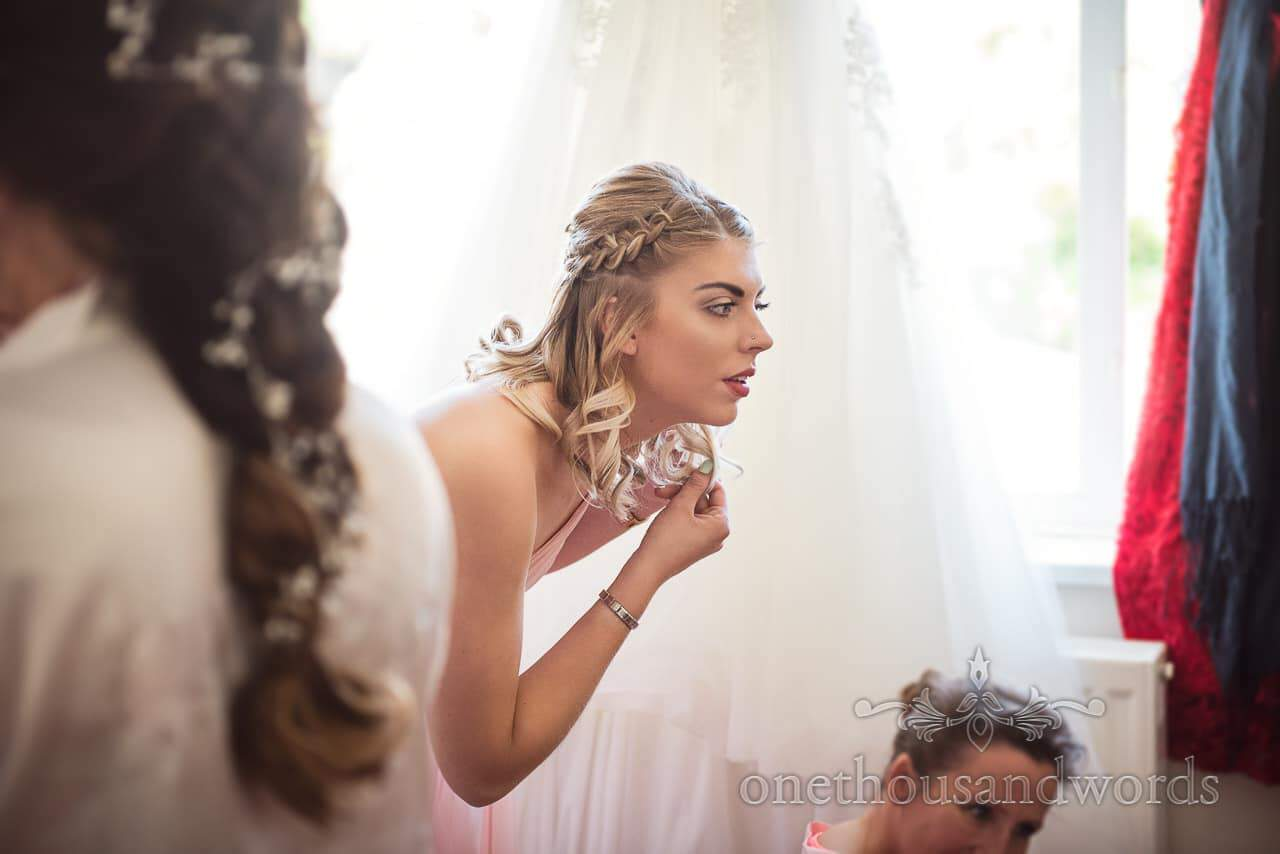 Bridesmaid in pink dress checks herself in mirror from Swanage Wedding Photos