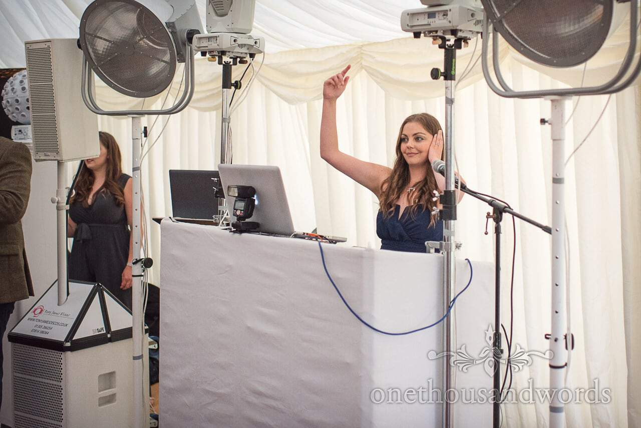 Bridesmaid mixing tunes behind futuristic white DJ console in wedding marquee