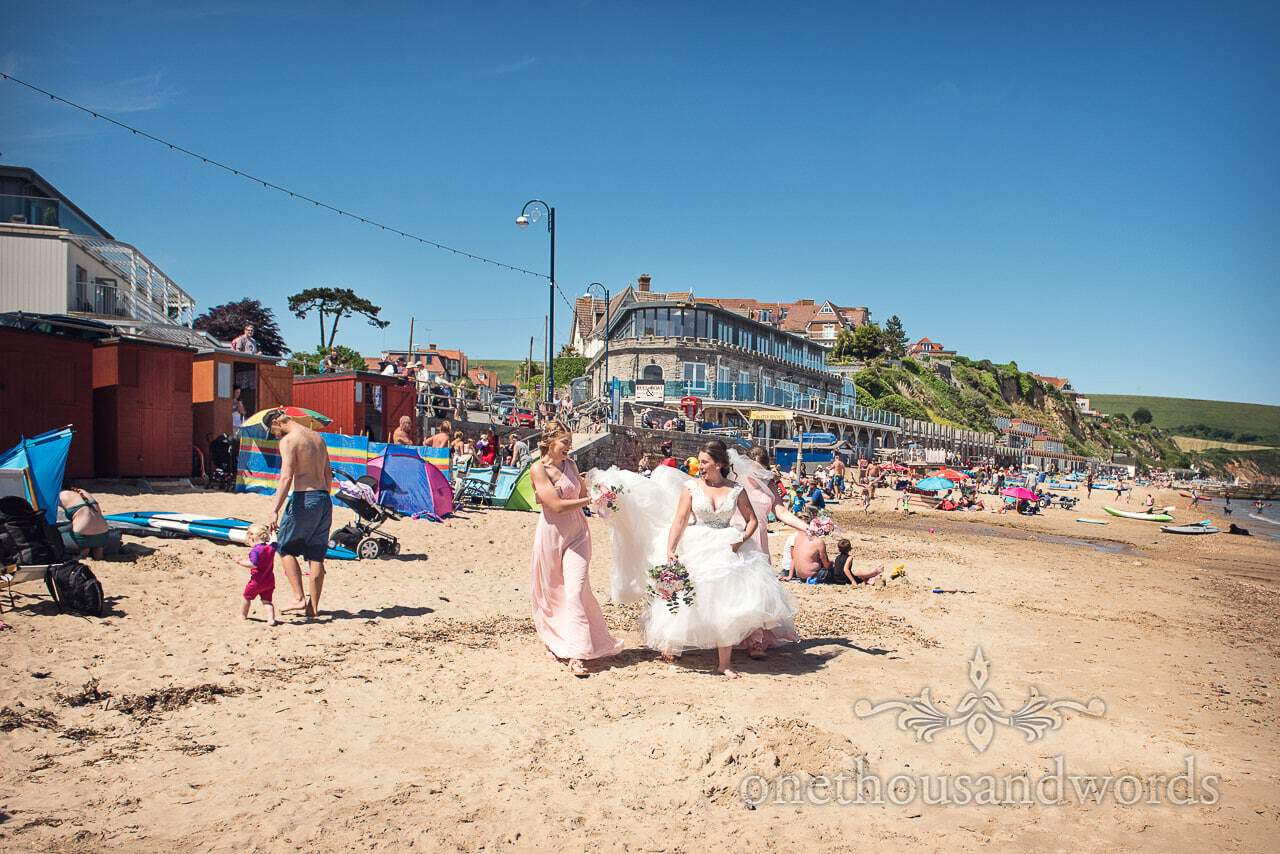 Bridesmaids help bride with dress on beach from Swanage Wedding Photos