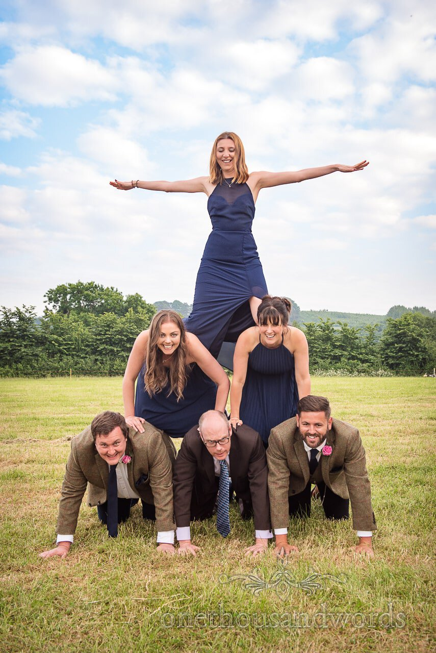 Bridesmaids in blue and groomsmen form human pyramid at countryside wedding