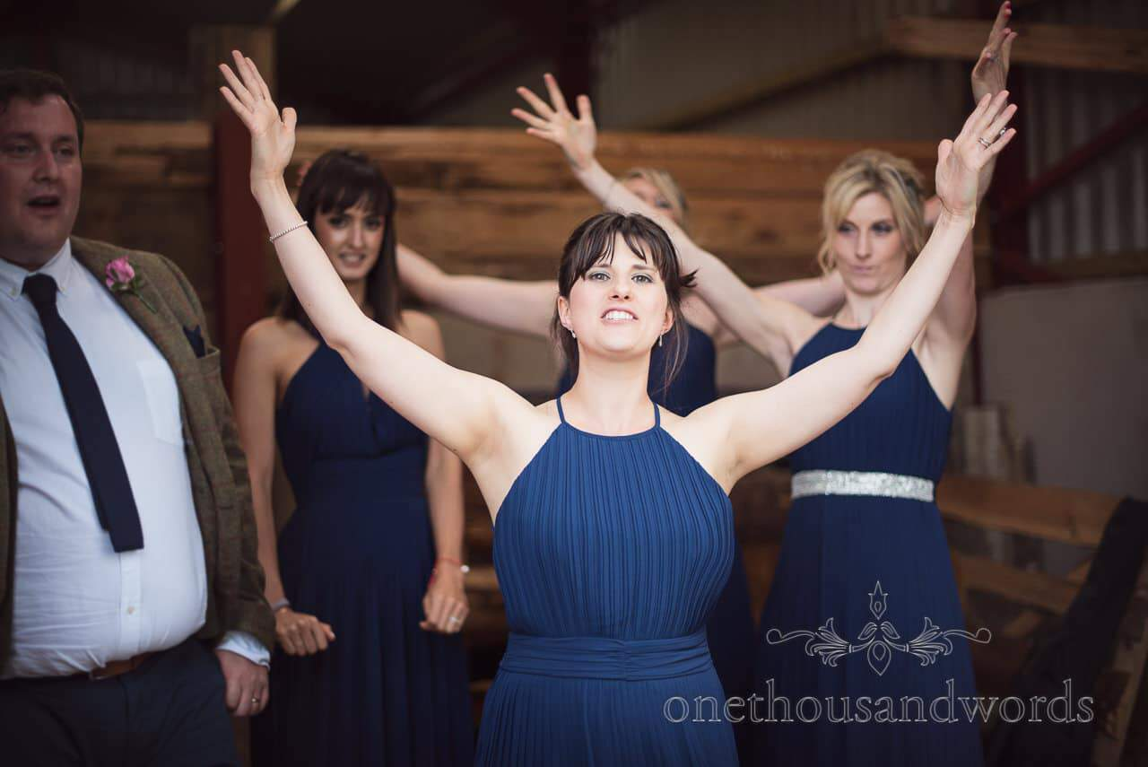 Bridesmaids in blue dresses in wedding barn raise their hands