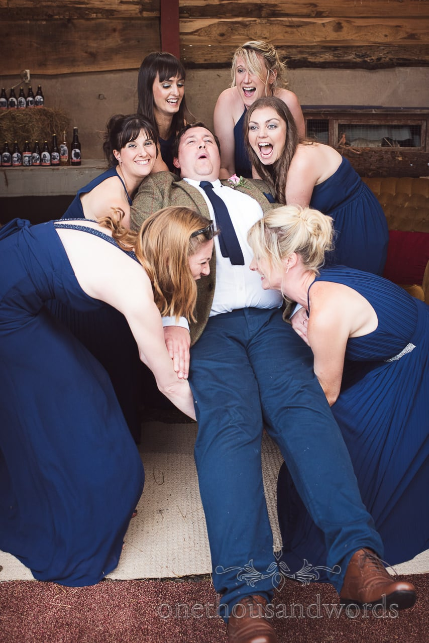 Bridesmaids in blue lift best man in barn from countryside wedding photos
