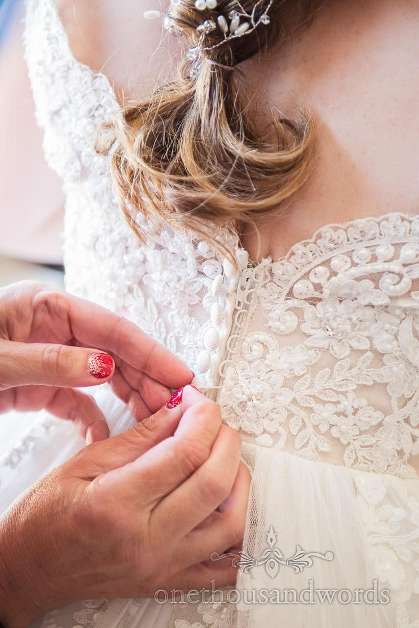 Buttons of wedding dress are done up from Swanage Wedding Photos