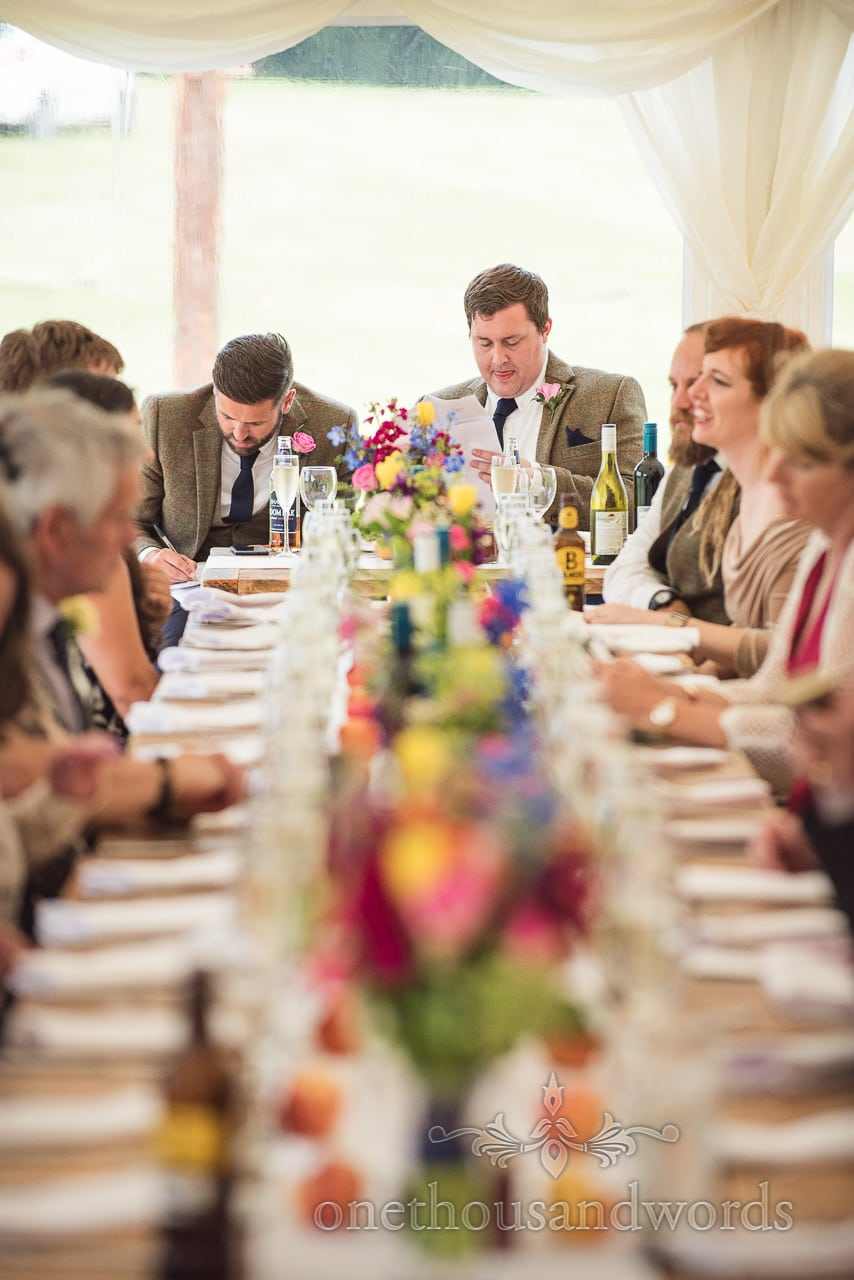 Countryside Wedding Photos of best men revising speeches at marquee reception