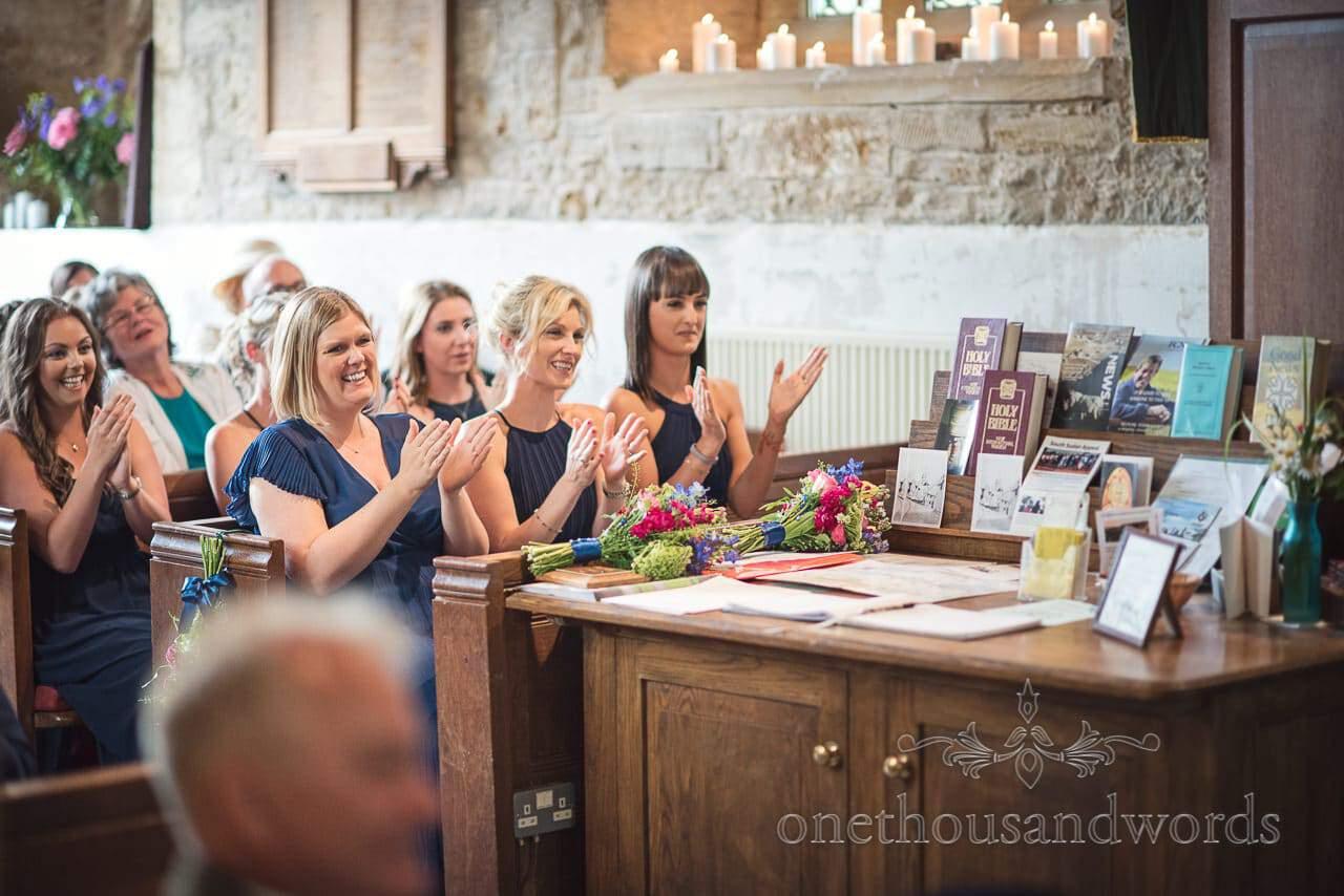 Countryside Wedding Photos of bridesmaids applause at church wedding