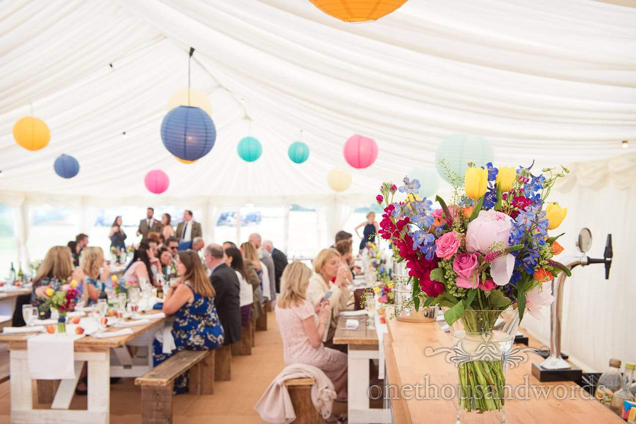 Countryside Wedding Photos of colorful arrangement on bar at marquee reception