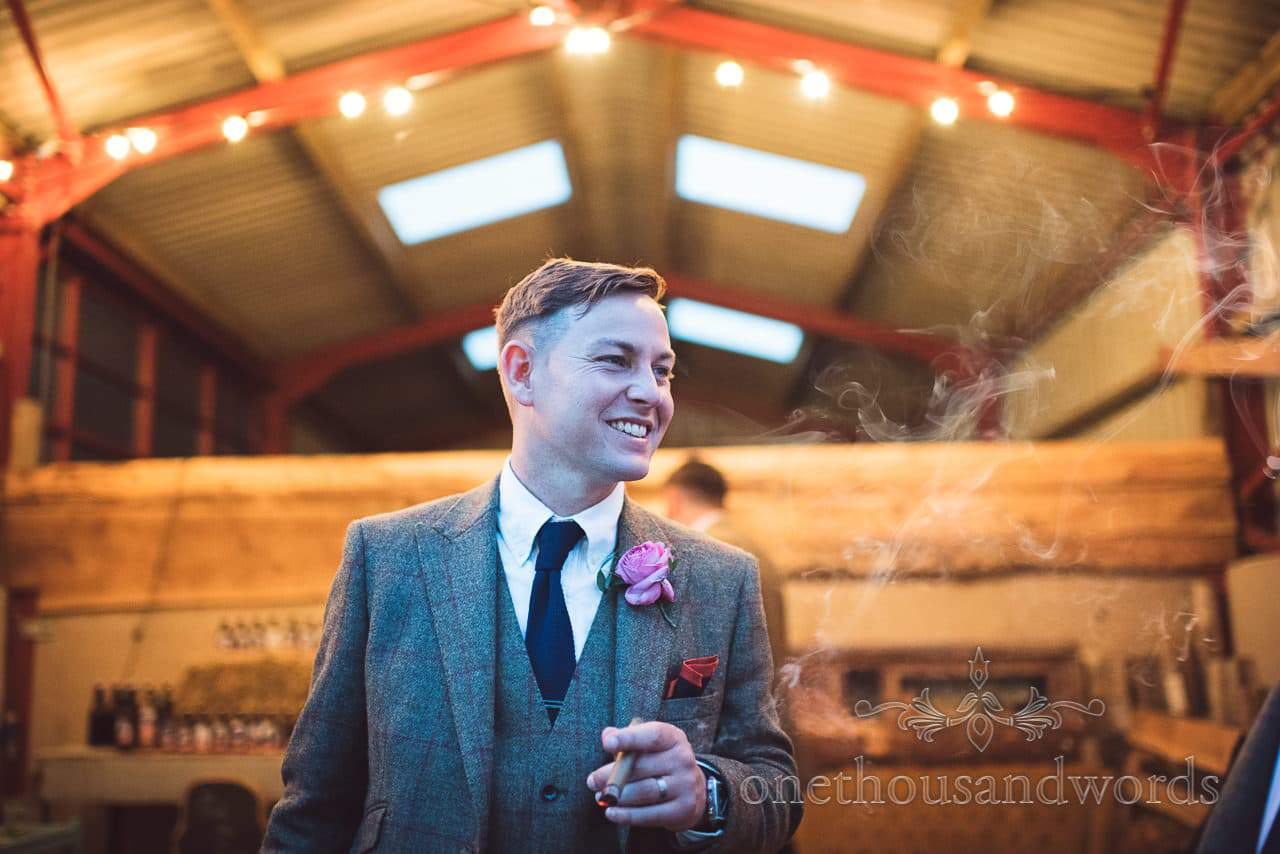 Countryside Wedding Photos of groom outside barn smoking a cigar on evening