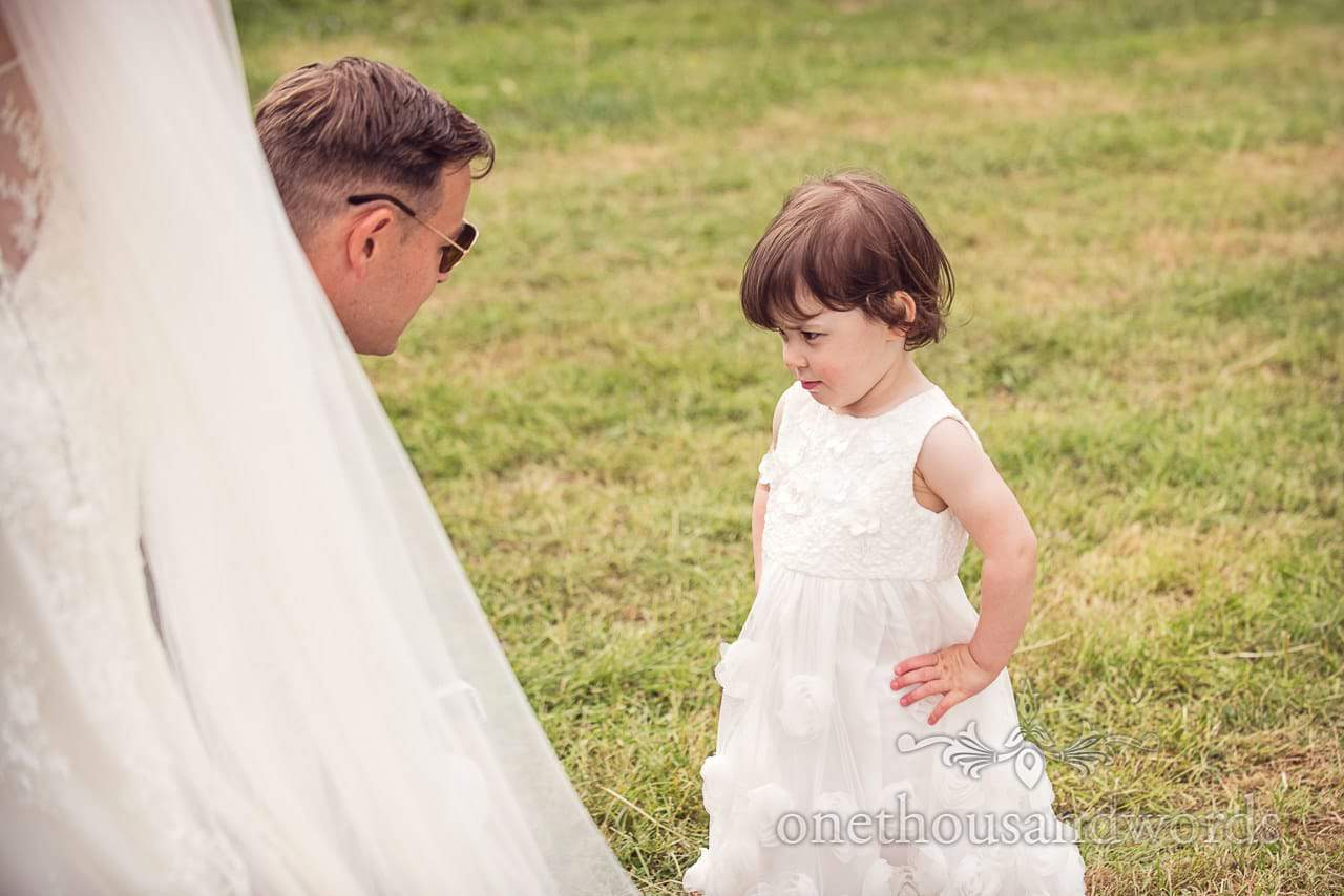 Countryside Wedding Photos of groom trying to reason with flower girl