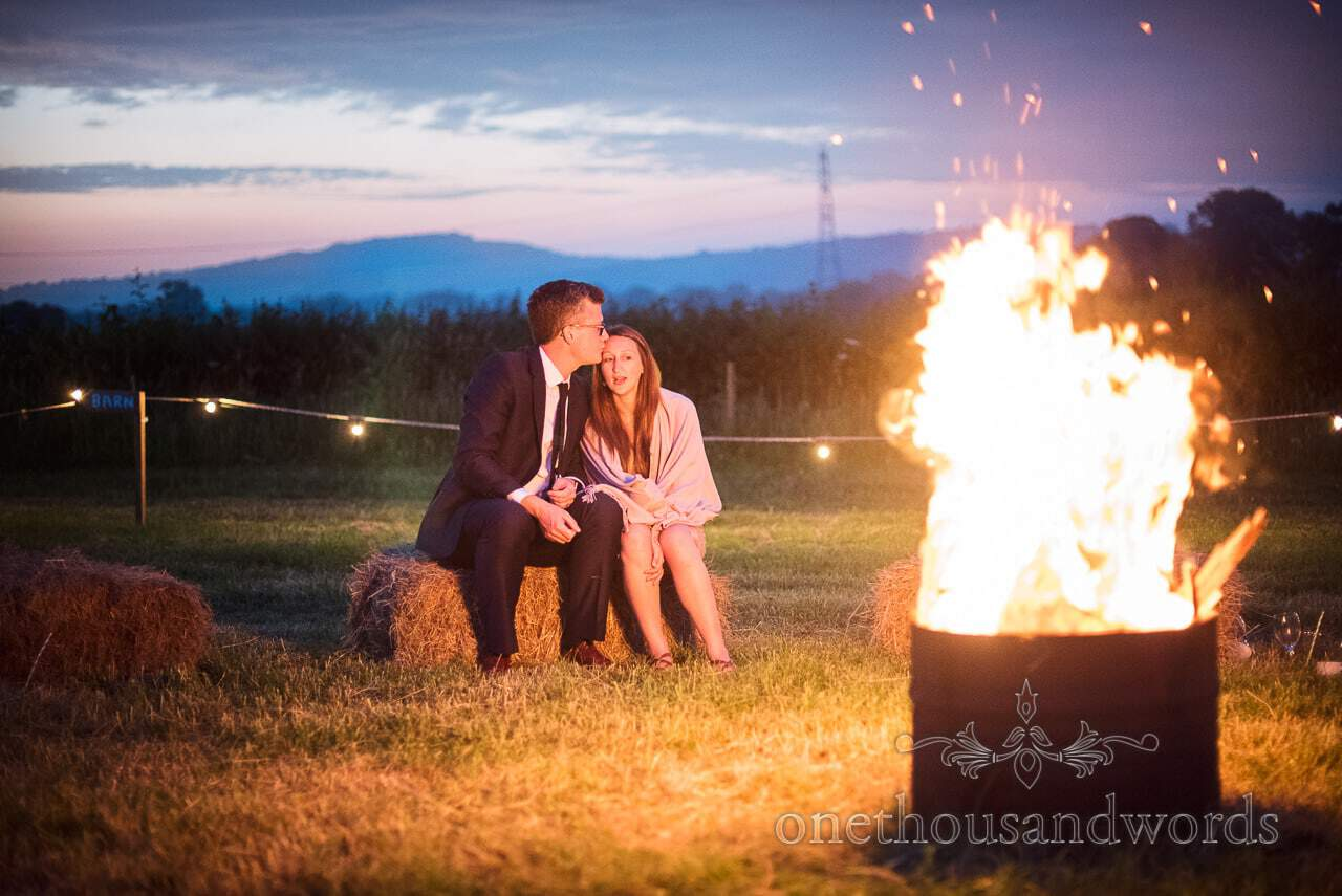 Countryside Wedding Photos of guests sitting on straw bales around fire pit