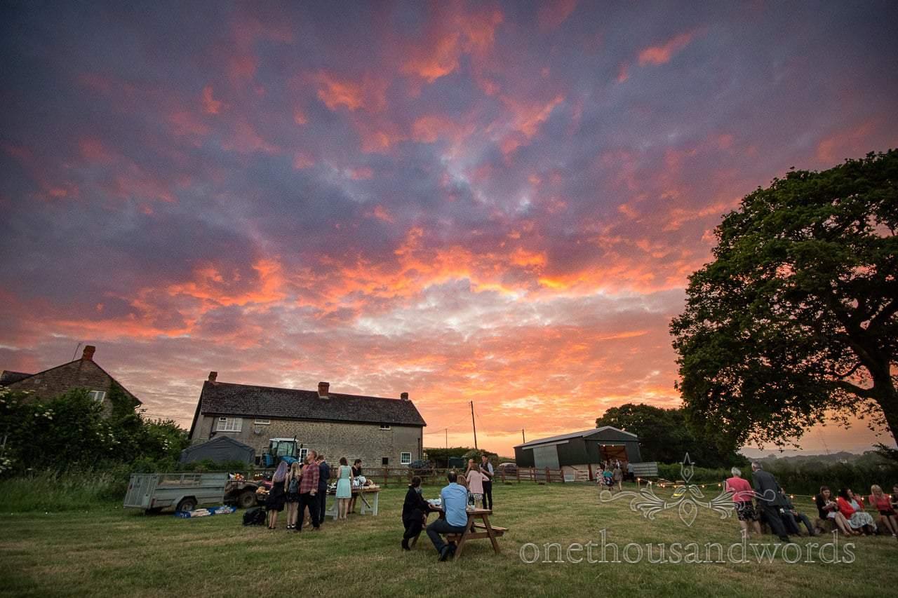 Countryside Wedding Photos of spectacular sunset over farmhouse wedding venue