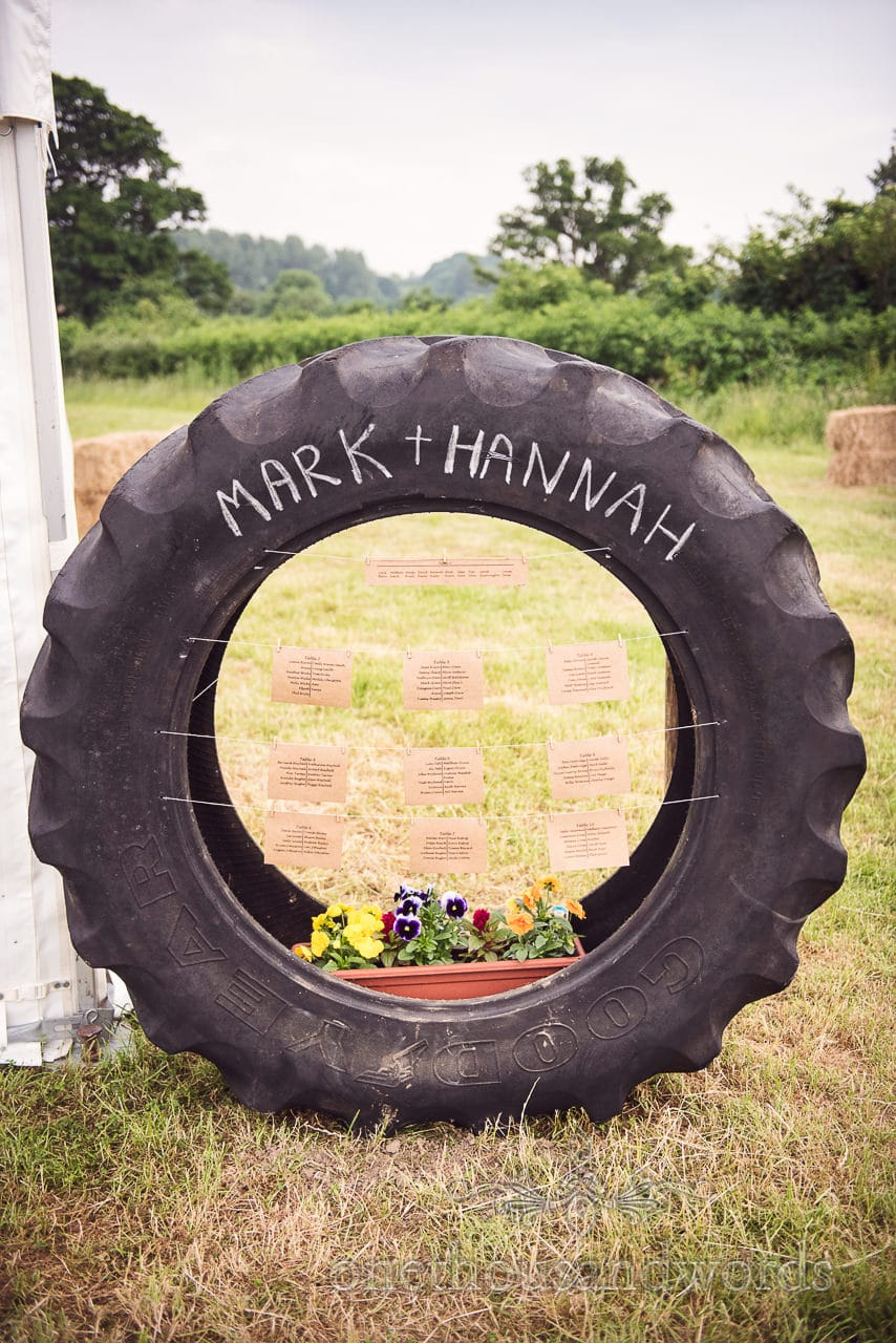 Countryside Wedding Photos of tractor Tyre table plan at marquee reception