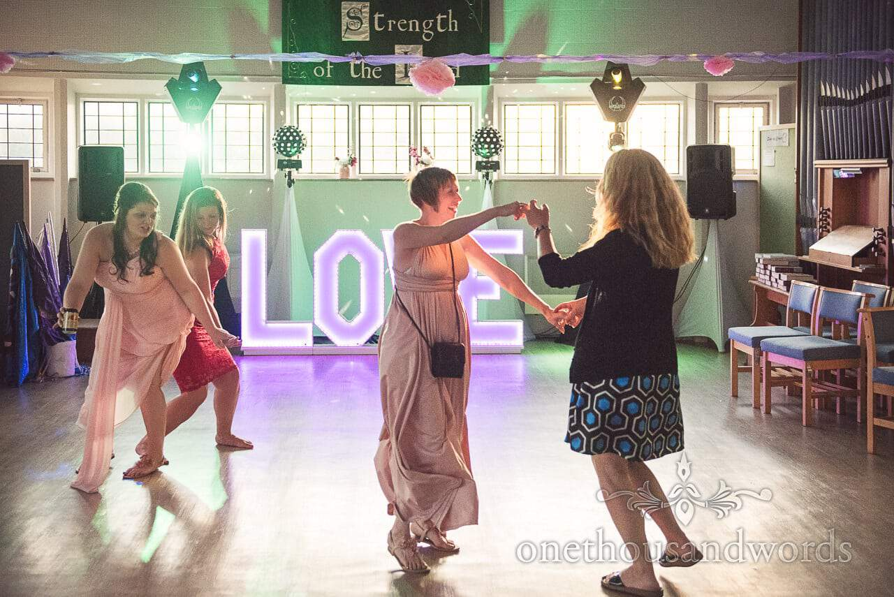 Dancing bridesmaids and guests during evening entertainment from Swanage wedding photos
