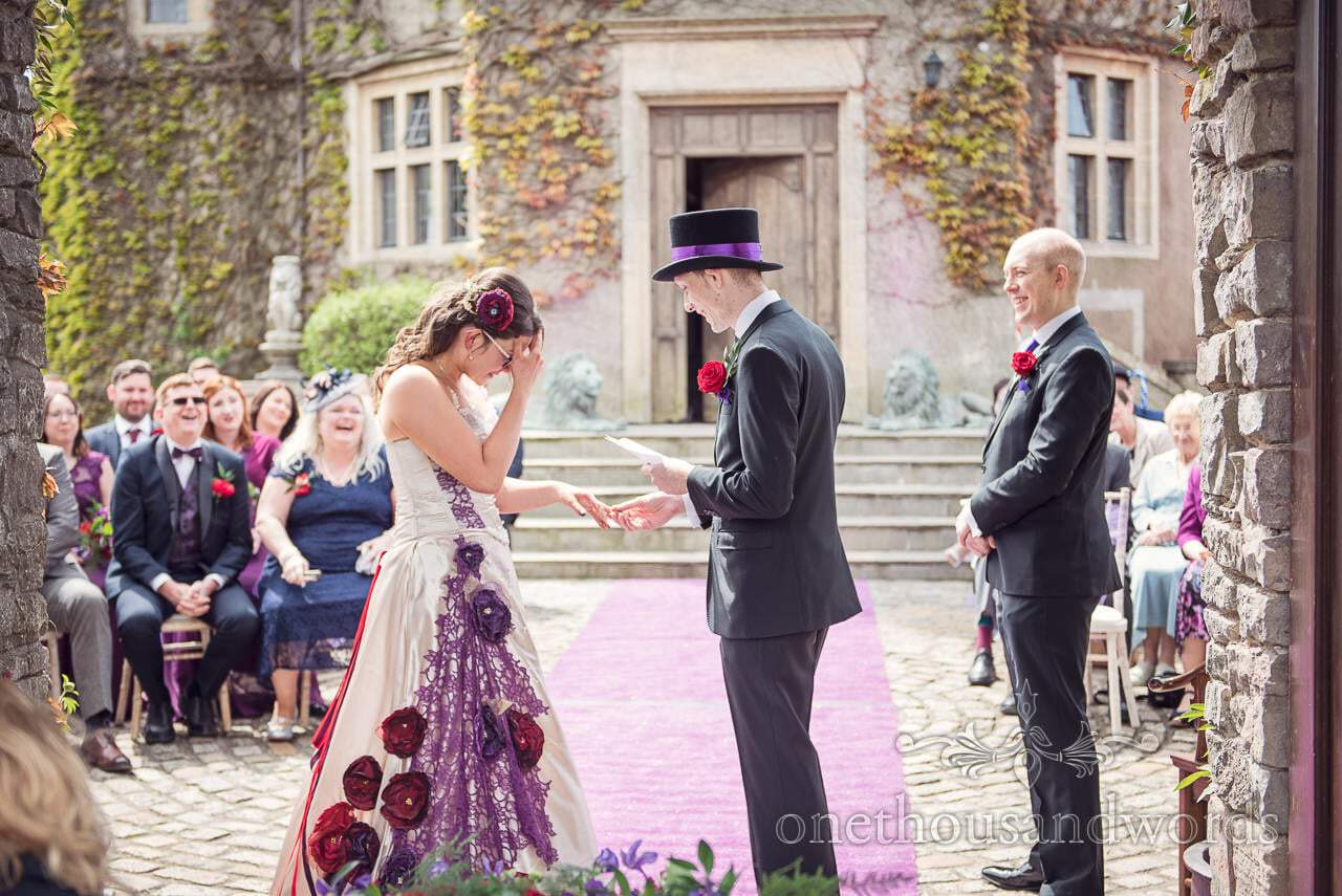 Embarrassed bride as groom reads vows during Walton Castle wedding